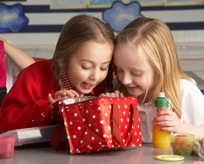 Primary School Pupils Enjoying Packed Lunch In Classroom